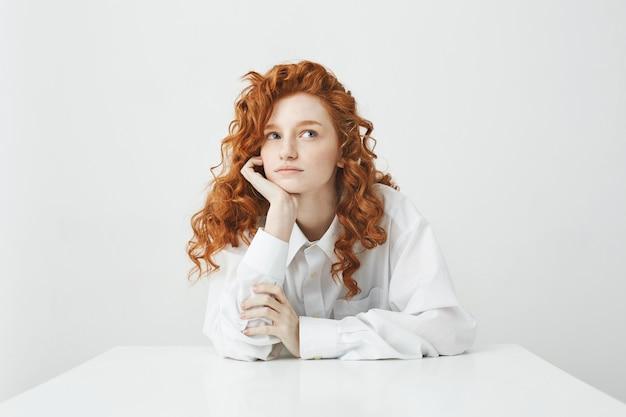 Marzycielska czuła młoda kobieta z rudymi kręconymi włosami myśli marzy siedząc na stole.