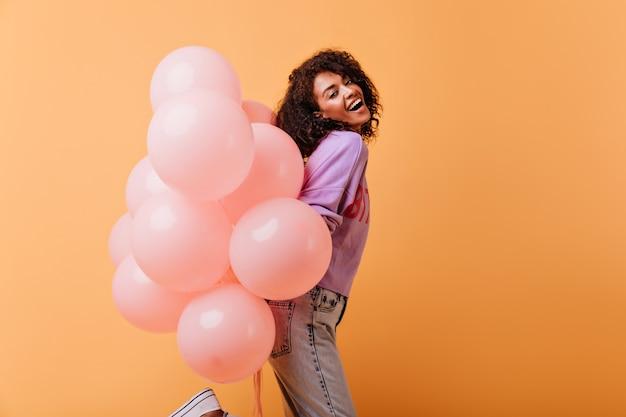 Marzycielska dama w swobodnym stroju tańcząca z wiązką balonów z helem. pogodna czarna dziewczyna przygotowuje się do przyjęcia urodzinowego.