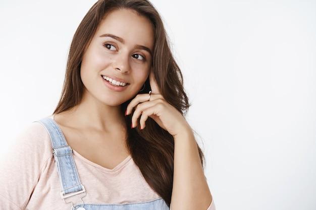 Marzycielska delikatna dziewczyna myśląca i mająca coś słodkiego i dobrego w myślach uśmiechnięta