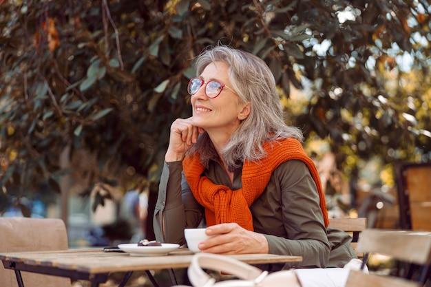Marzycielska dojrzała dama w okularach siedzi opierając się na dłoni przy stole na tarasie kawiarni na świeżym powietrzu