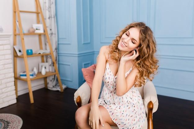 Marzycielska dziewczyna o blond kręconych włosach siedzi na fotelu w studio z niebieskimi ścianami i brązowymi meblami