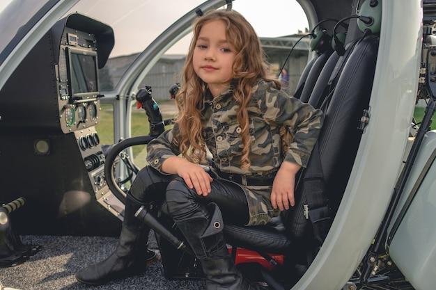 Marzycielska dziewczyna siedząca w otwartym kokpicie helikoptera