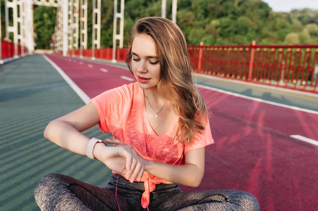 Marzycielska dziewczyna sportowa patrząc na zegarek po treningu. zewnątrz strzał wyrafinowanej kobiety relaks przed maratonem na stadionie.