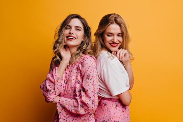 Marzycielska dziewczyna w różowej bluzce pozuje z siostrą. kochane koleżanki śmieją się na żółtej ścianie.
