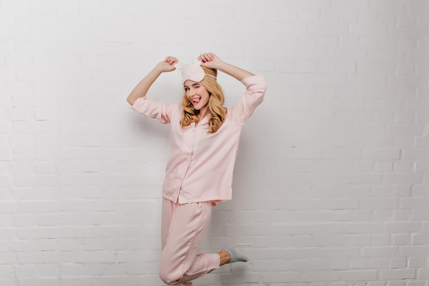 Marzycielska dziewczyna w szarych skarpetkach tańczy z wysuniętym językiem rano. romantyczna młoda kobieta w bawełnianej piżamie i różowej masce na oczy, dobrze się bawi.