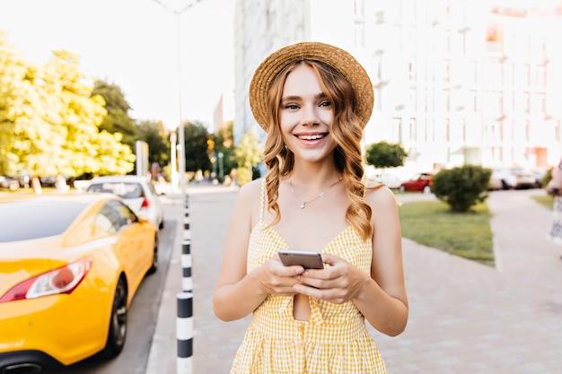 Marzycielska dziewczyna w żółtej sukience vintage wyrażająca pozytywne emocje podczas spaceru. niesamowita kobieta z falowanymi włosami, trzymając smartfon.