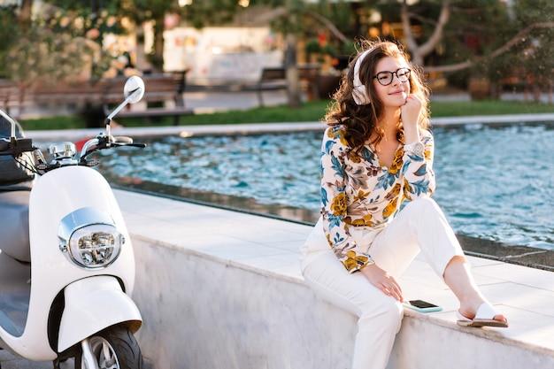 Marzycielska dziewczyna z elegancką fryzurą słuchająca muzyki i odwracająca wzrok, spędzająca czas w pobliżu fontanny