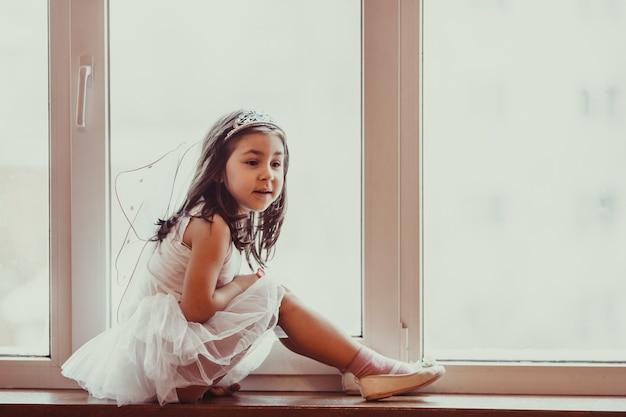 Marzycielska dziewczynka w różowej tutu tańczy wygląda przez okno