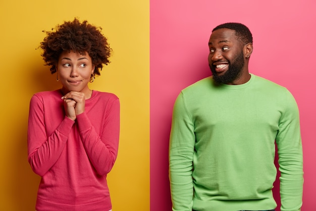 Marzycielska etniczna kobieta trzyma ręce pod brodą, patrzy na bok, nosi różowy sweter, zadowolony brodacz patrzy na swoją dziewczynę, uśmiecha się radośnie. ludzie wyrażają pozytywne emocje, stoją razem w pomieszczeniach.