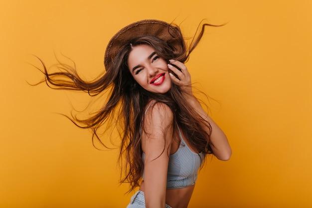 Marzycielska kaukaska dziewczyna z długimi fryzurami szczęśliwy taniec z jasnym wnętrzem