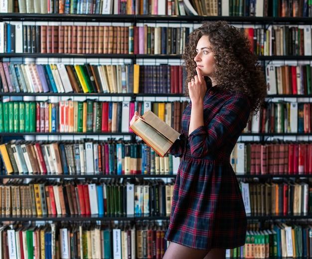 Marzycielska kędzierzawa brunetki dziewczyna trzyma książkę w jej ręce, stoi przeciw tłu półki z książkami i patrzeje daleko od