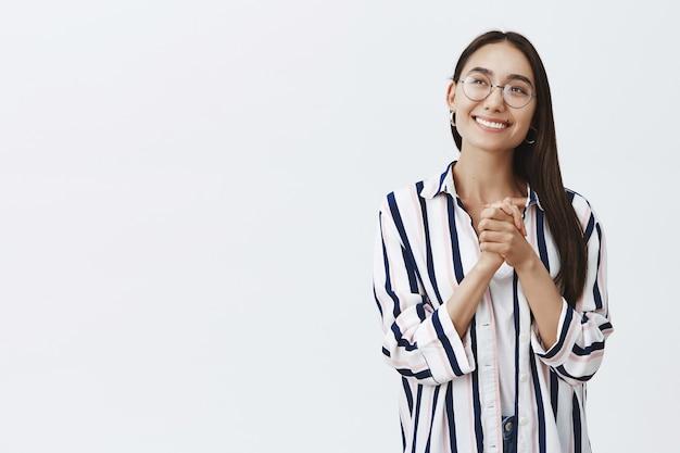Marzycielska kobieca kobieta w modnych okularach i bluzce w paski, patrząca z zachwytem i podziwem w lewy górny róg, ściskająca dłonie na piersi i wyobrażająca sobie przyjemny sen na szarej ścianie