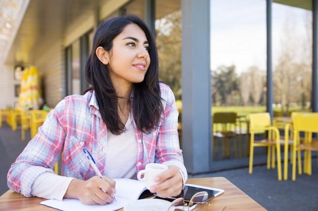 Marzycielska kobieta robi notatki w plenerowej kawiarni