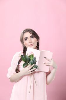 Marzycielska kobieta trzyma róże i książkę