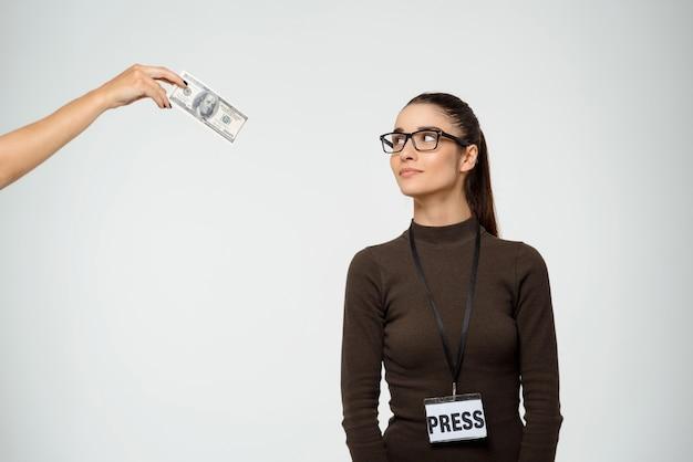 Marzycielska kobieta uśmiecha się jak patrząc na łapówki dolarów