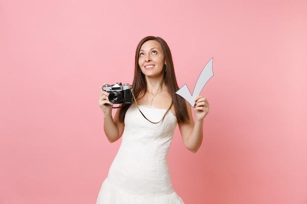Marzycielska kobieta w białej sukni patrząc w górę trzymaj retro vintage aparat fotograficzny i znacznik wyboru, wybierając fotografa personelu