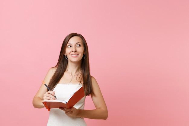 Marzycielska kobieta w białej sukni patrząca w górę napisz notatkę w notatniku