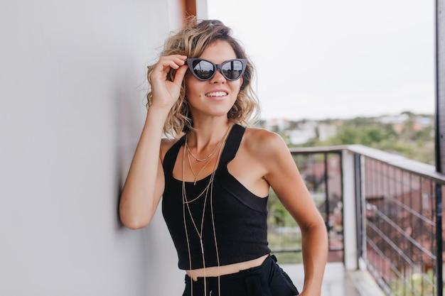 Marzycielska kobieta w czarnym podkoszulku dotykająca okularów przeciwsłonecznych podczas sesji zdjęciowej na balkonie. całkiem kaukaski pani stojąca na tarasie z uroczym uśmiechem.