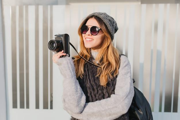 Marzycielska kobieta w okularach przeciwsłonecznych z aparatem w ręku, patrząc z czarującym uśmiechem. odkryty portret inspirowanej fotografki w kapeluszu i miękkim swetrze z dzianiny.