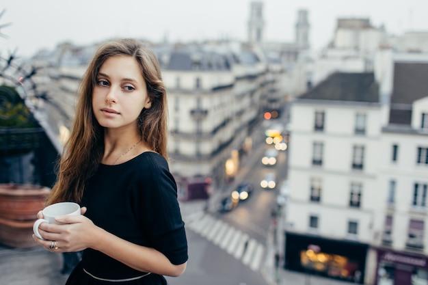 Marzycielska kobieta z kubkiem na balkonie