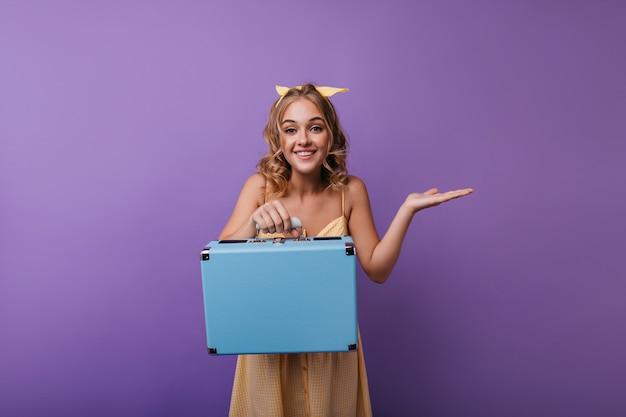 Marzycielska kręcona dziewczyna w żółtym stroju z bagażem. portret modelki debonair z walizką uśmiecha się do kamery.