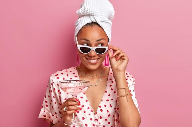 Marzycielska ładna ciemnoskóra kobieta trzyma dłonie na okularach, pije alkohol, patrzy na bok z uśmiechem, nosi jedwabną suknię, zawinięty ręcznik