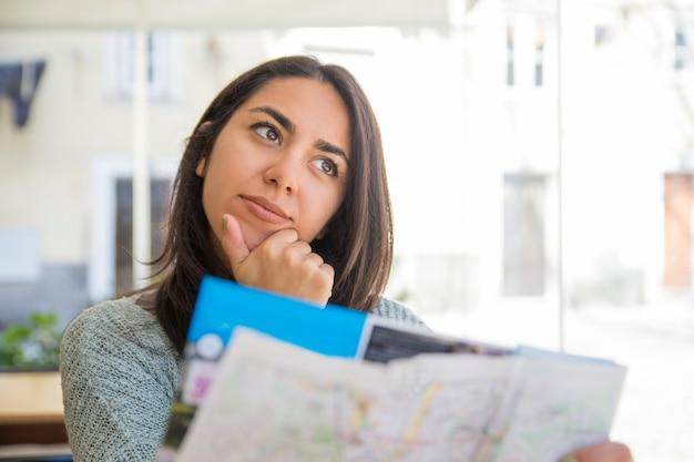 Marzycielska ładna młoda kobieta używa papierową mapę w kawiarni