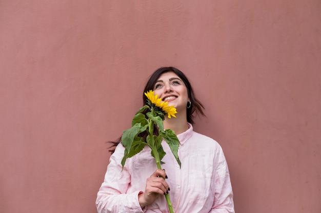 Marzycielska młoda dziewczyna z jaskrawym słonecznikiem
