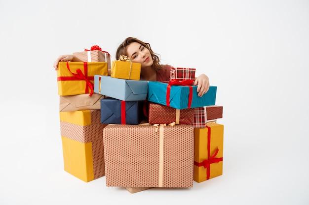 Marzycielska młoda kędzierzawa kobieta wśród prezentowych pudeł