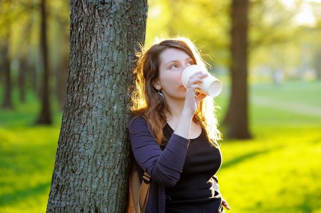 Marzycielska młoda kobieta pije kawę lub herbaty outdoors