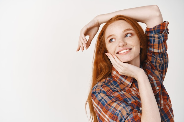 Marzycielska nastolatka z rudymi naturalnymi włosami, pozująca na białej ścianie i patrząca w lewo na logo, dotykająca idealnej twarzy bez makijażu