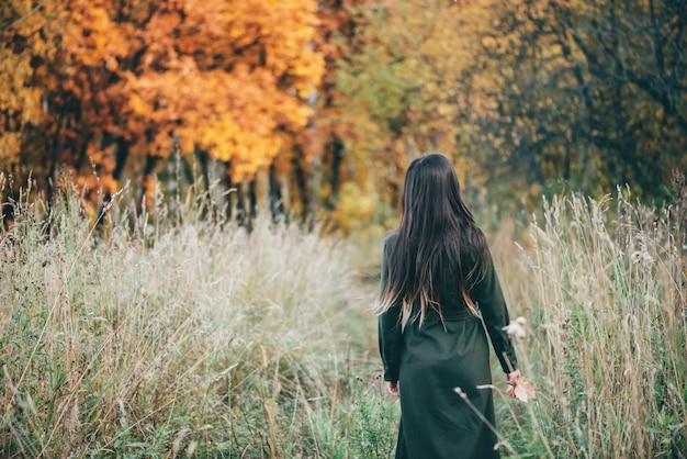 Marzycielska piękna dziewczyna z długimi naturalnymi czarnymi włosami na tle z kolorowymi liśćmi.