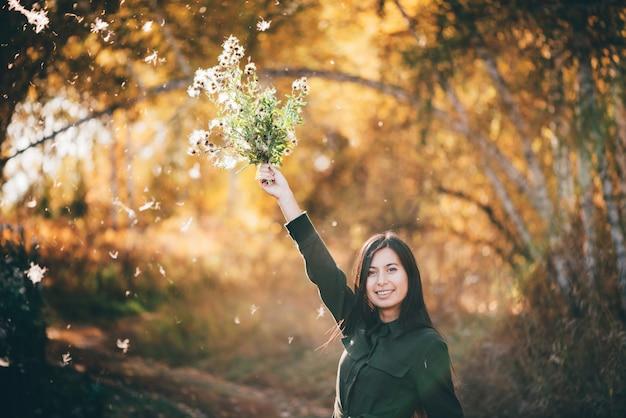 Marzycielska piękna dziewczyna z osetem kwitnie na bokeh tle z żółtymi liśćmi.