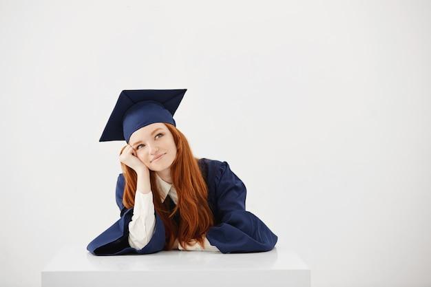 Marzycielska piękna kobieta absolwent uśmiecha się myślenia.
