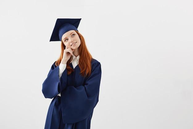 Marzycielska piękna kobieta absolwentka myśląca śni.