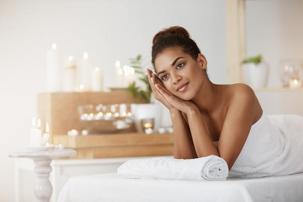 Marzycielska piękna kobieta odpoczywa w zdroju salonie w ręczniku.