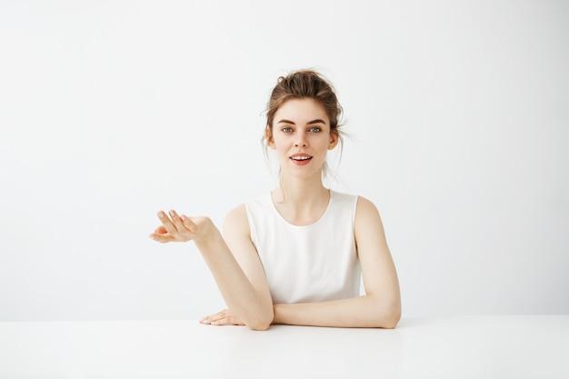 Marzycielska piękna młoda kobieta z babeczki obsiadaniem przy stołem nad białym tła myśleć marzyć.