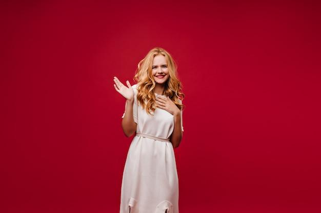 Marzycielska pogodna pani pozująca w białej sukni. ekstatyczna dziewczyna długowłosy na białym tle na czerwonej ścianie.