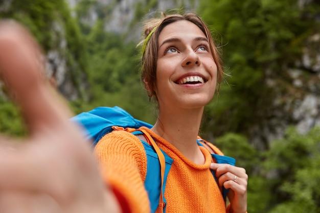Marzycielska pozytywna młoda kobieta skupiona w górę, sprawia, że portret selfie