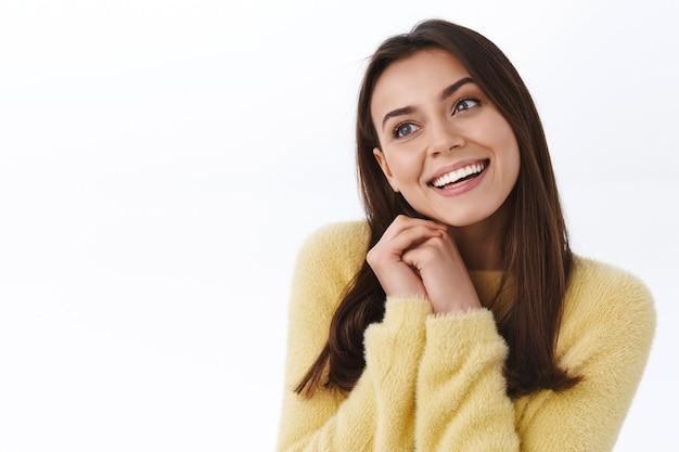 Marzycielska romantyczna kobieta w żółtym swetrze marząca o czymś pięknym, idealnej randce w piękny wiosenny dzień, patrząc na bok zamyślona i uśmiechnięta beztrosko, koncepcja szczęścia