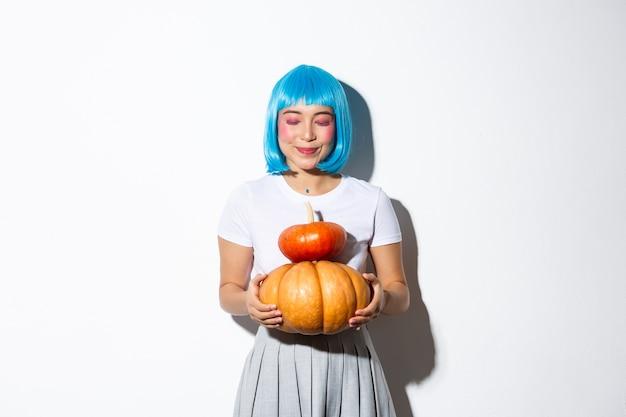 Marzycielska śliczna azjatka stojąca z dwoma dyniami w niebieskiej peruce i kostium na halloween, uśmiechnięta z zamkniętymi oczami.