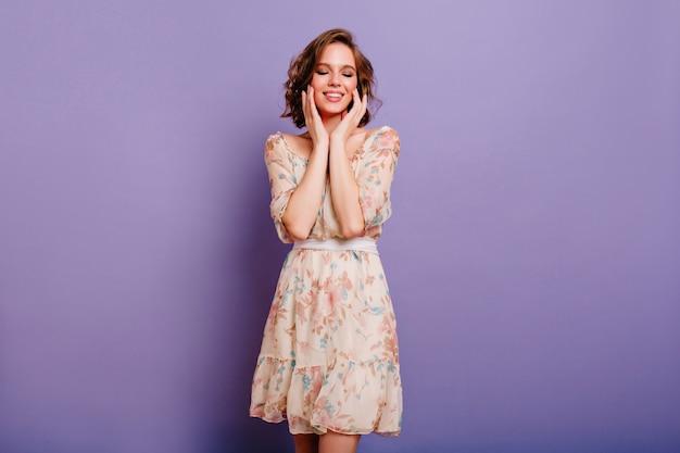 Marzycielska śliczna dziewczyna z modnym makijażem delikatnie dotykając jej twarzy, pozując na fioletowym tle