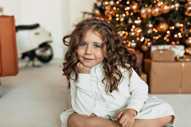 Marzycielska śliczna mała dziewczynka z lokami ubrana w biały sweter z dzianiny siedzi przed choinką i czeka na świętego mikołaja