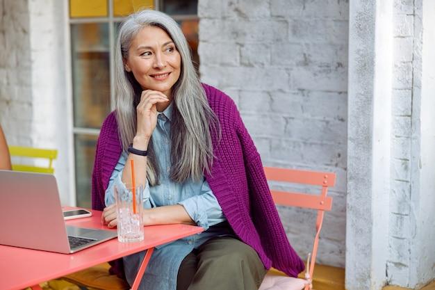 Marzycielska starsza azjatycka kobieta siedzi przy stole z komputerem i pije na tarasie kawiarni