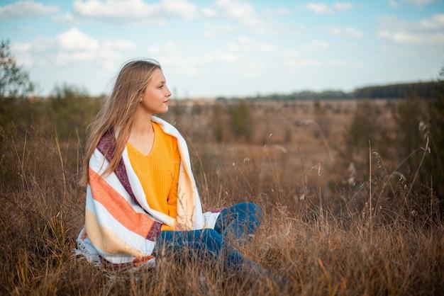 Marzycielska uczennica siedząca na polu z żółtymi suszonymi kwiatami i trawą późną jesienią