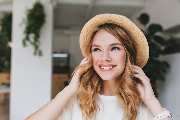 Marzycielska uśmiechnięta dziewczyna o bladej skórze, patrząca w górę i dotykająca jasnych loków