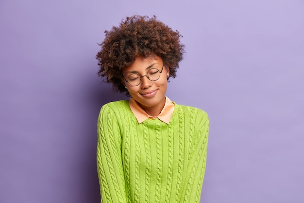 Marzycielska zadowolona młoda afro amerykanka stoi z zamkniętymi oczami i uśmiecha się delikatnie