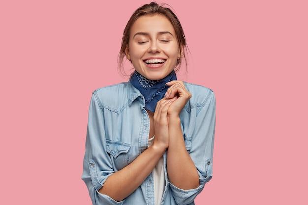 Marzycielska, zadowolona młoda dziewczyna ma zamknięte oczy, szeroko się uśmiecha, trzyma razem dłonie, wyobraża sobie coś przyjemnego