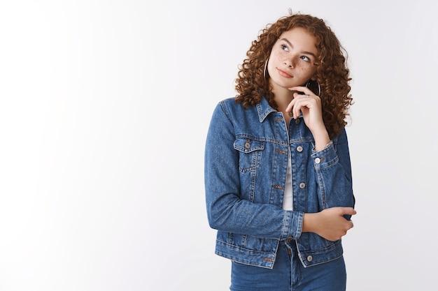 Marzycielska zamyślona urocza ruda dziewczyna z kręconymi włosami ubrana w dżins szczupła głowa spojrzenie górny lewy róg myślenie podejmowanie decyzji decyzja o tym, jakie jedzenie zamówić, stojąc białe tło zrelaksowany chłód