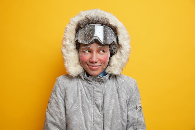 Marzycielska zimowa dziewczyna z czerwoną zmarzniętą twarzą cieszy się wakacjami w górskim kurorcie podczas mroźnego, śnieżnego dnia przykryta płatkami śniegu ubrana w ciepłą kurtkę z kapturem nosi gogle narciarskie lubi sporty ekstremalne.